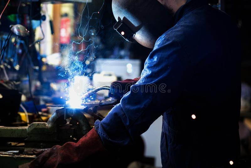 Spawacz spawa w garażu, przemysłowego pracownika robotnik przy fabryczną spawalniczą stalową strukturą zdjęcie stock