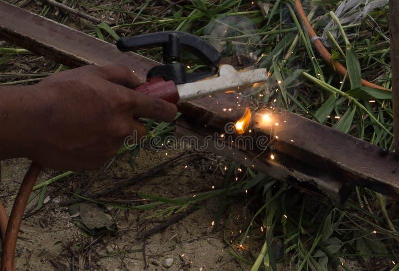 Spawacz używa elektrodowego spaw stalowa rama z spawalniczą maszyną, Spawający iskrę zaświeca i dymi obrazy royalty free