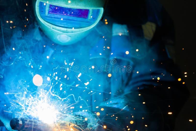 Spawacz w hełmie pracuje w sklepie Jaskrawe iskry od metalu spawu obrazy stock