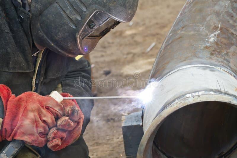 Spawacz wykonuje spaw pracy na rurociąg stali nierdzewnej fotografia stock