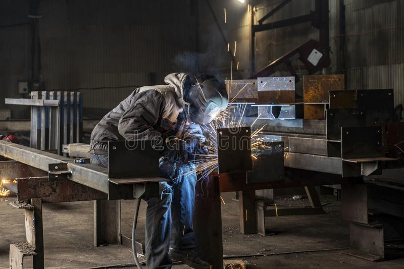 Spawający z iskrami procesem upłynniającym rdzeniował łuku spaw, Przemysłowa stalowa spawacz część w fabrycznym spawaczu Przemysł zdjęcia royalty free