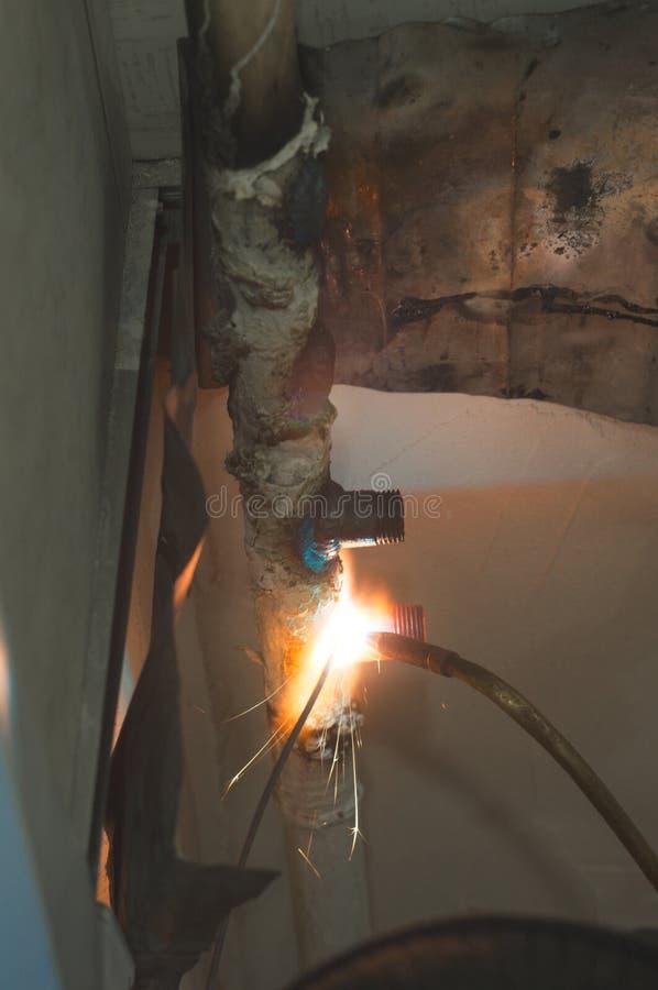 Spawalnicza praca w domu Mistrz spawa benzynowe tubki z benzynową pochodnią, łączy stopionego gorącego metal fotografia stock