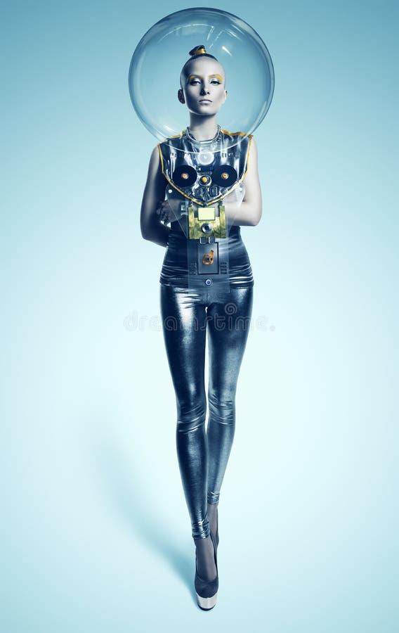 Spazi la donna che sta nel vestito e nel casco d'argento fotografia stock