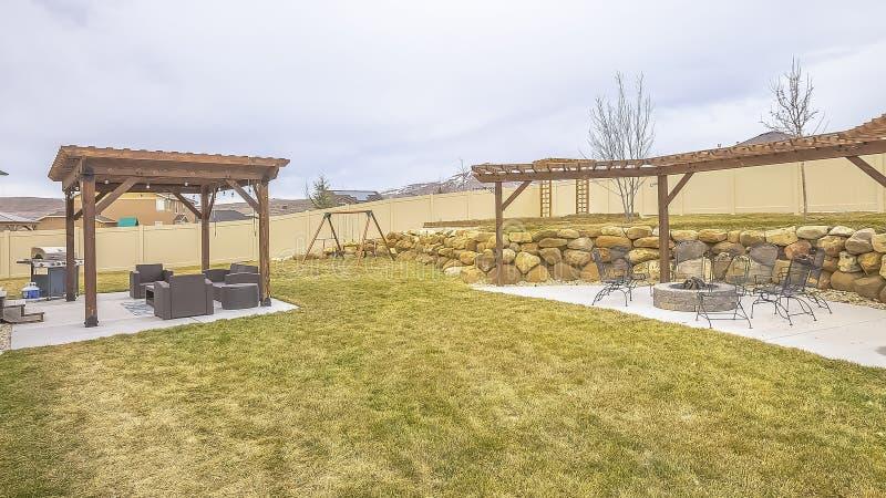 Spazi vitali e campo da giuoco all'aperto della struttura di panorama all'iarda spaziosa ed erbosa di una casa immagine stock