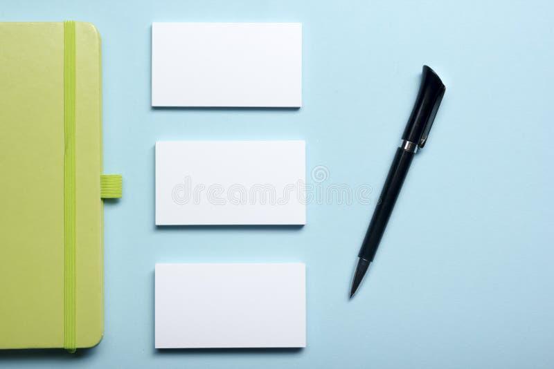 Spazio in bianco del biglietto da visita, blocco note, fiore, tazza di caffè e penna alla vista del piano d'appoggio della scriva immagini stock libere da diritti