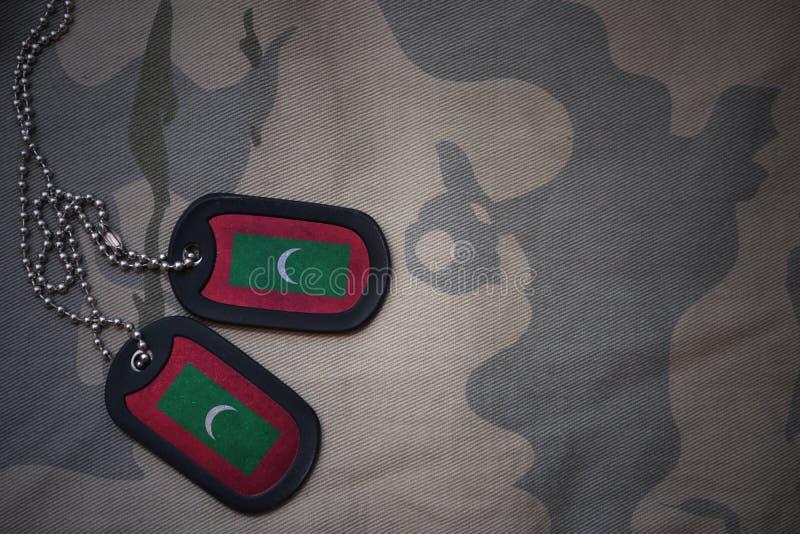 Spazio in bianco dell'esercito, medaglietta per cani con la bandiera delle Maldive sui precedenti cachi di struttura immagini stock libere da diritti