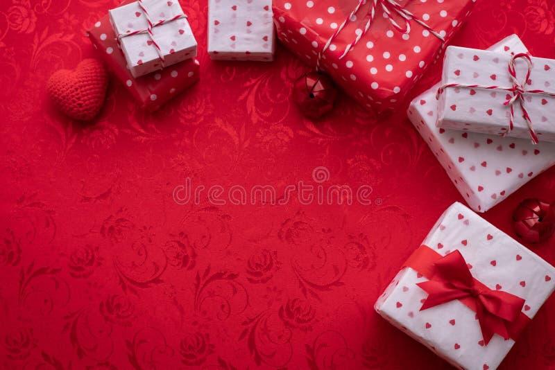 Spazio della copia sulla tovaglia rossa con il contenitore di regalo dei biglietti di S. Valentino, fondo di celebrazione di San  immagini stock libere da diritti