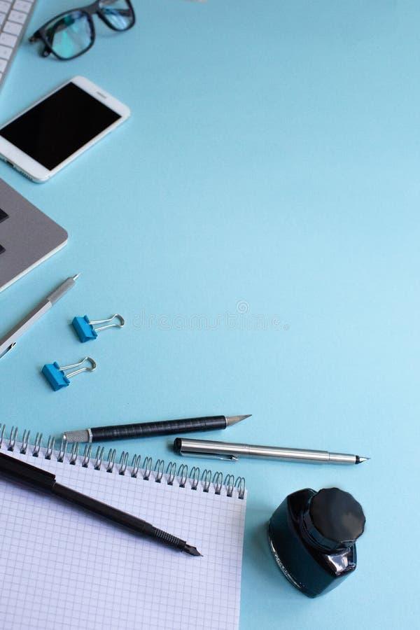 Spazio di funzionamento con il computer portatile, lo smartphone, la penna, i vetri ed il taccuino su fondo pastello blu Fondo bl fotografie stock