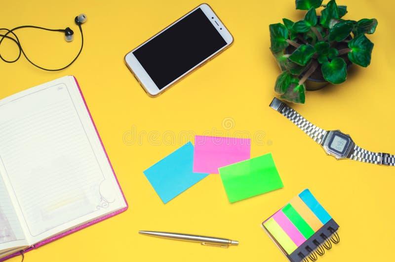 Spazio di funzionamento con un taccuino, penna, orologio, telefono, cuffie su un fondo giallo Posto per testo Lo spazio di funzio immagine stock