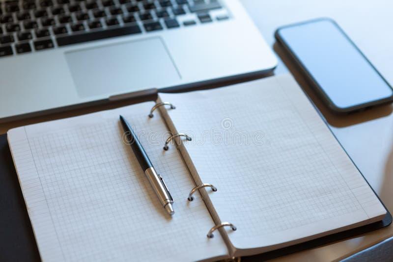 Spazio di funzionamento, vista superiore Computer portatile, telefono cellulare e taccuino aperto con la penna sul desktop beige fotografie stock libere da diritti