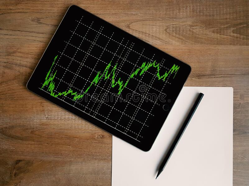 Spazio Grey Ipad Air With Graph sulla Tabella di legno di Brown immagini stock libere da diritti