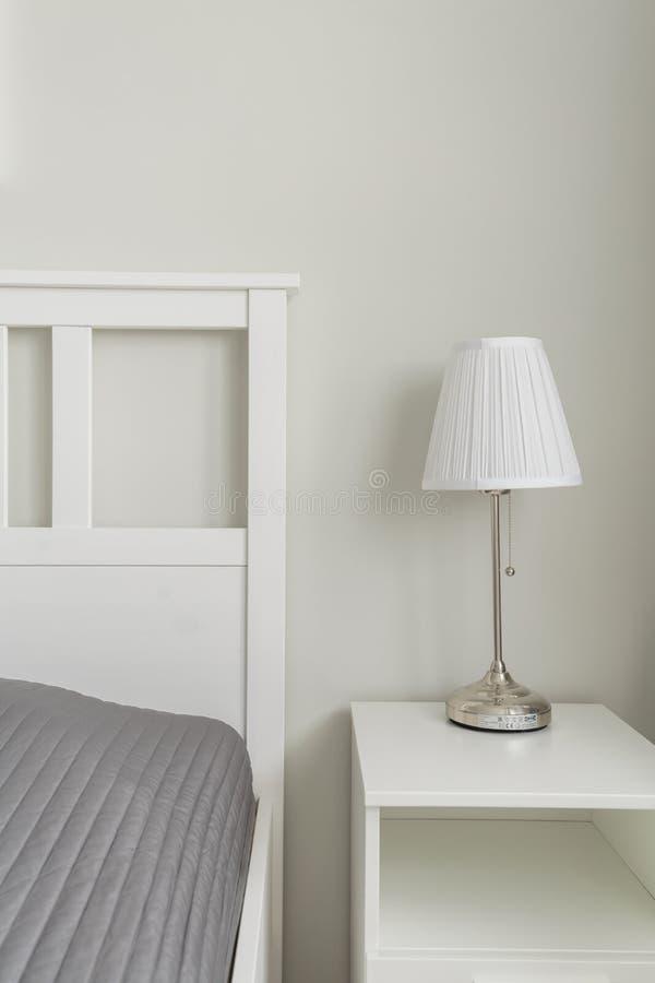 Spazio semplicemente progettato vicino al letto immagini stock libere da diritti