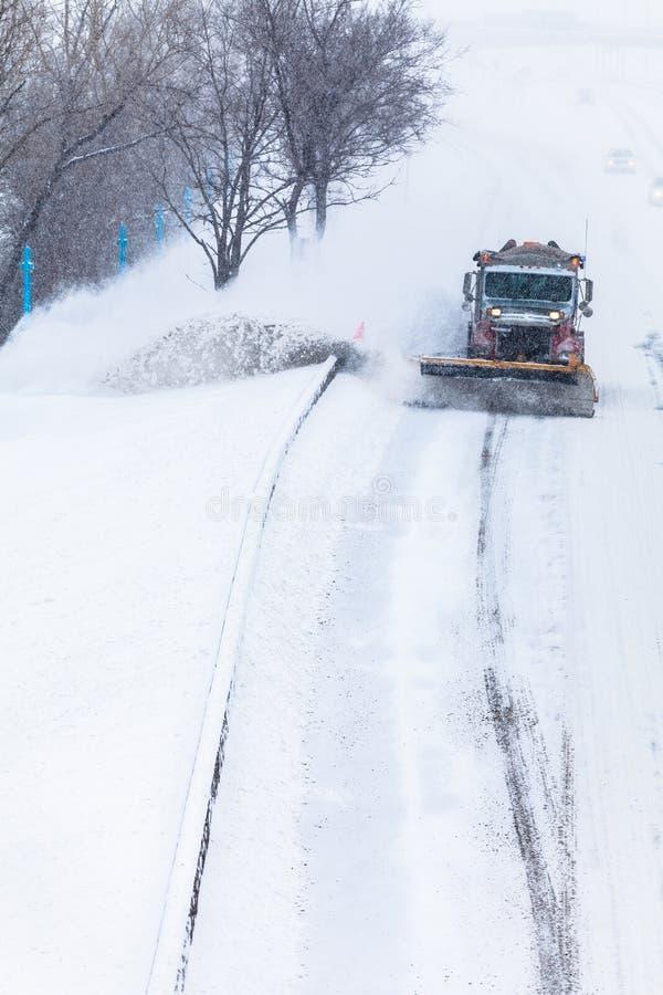 Spazzaneve che rimuove la neve dalla strada principale durante la bufera di neve immagine stock