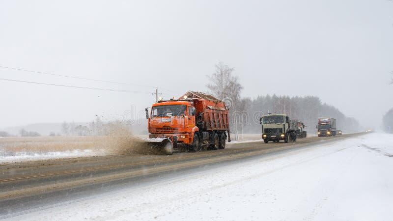 Spazzaneve che rimuove neve dalla strada di città fotografie stock