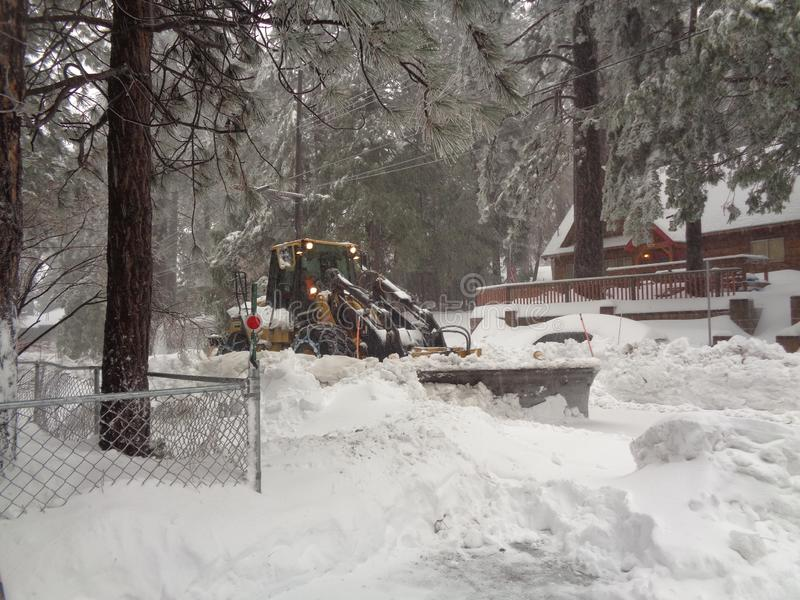 Spazzaneve che rimuove via residenziale nell'eseguire le primavere, San Bernardino Mountains CA immagine stock