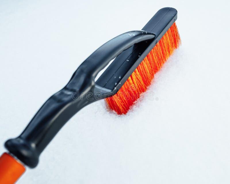 Spazzola arancio della neve per l'automobile, fondo dei fiocchi di neve immagine stock libera da diritti