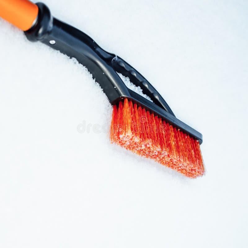 Spazzola arancio della neve per l'automobile, fondo dei fiocchi di neve fotografia stock