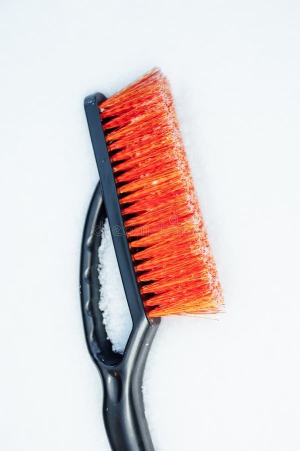 Spazzola arancio della neve per l'automobile, fondo dei fiocchi di neve fotografie stock libere da diritti