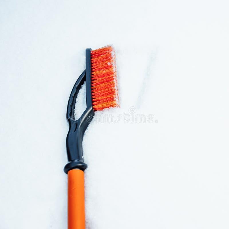 Spazzola arancio della neve per l'automobile, fondo dei fiocchi di neve immagini stock libere da diritti