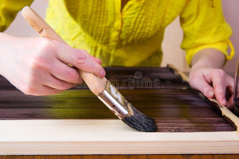 Spazzola con il primo piano scuro della pittura su un fondo leggero Verniciatura del bordo di legno fotografia stock