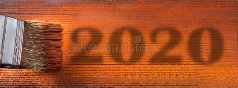 Spazzola con vernice Nuovo anno 2020 bordo blu della pittura dell'uomo nel pennello marrone Concetto di nuovo anno Ombra immagini stock