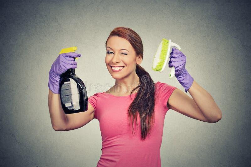 Spazzola della tenuta della donna e bottiglia felici della soluzione di pulizia del detersivo immagine stock