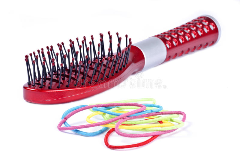 Spazzola di capelli rossa ed elastici variopinti fotografie stock libere da diritti