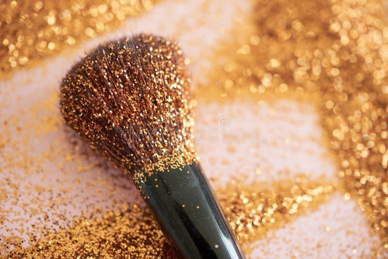 Spazzola di trucco con scintillio dorato scintillante immagini stock