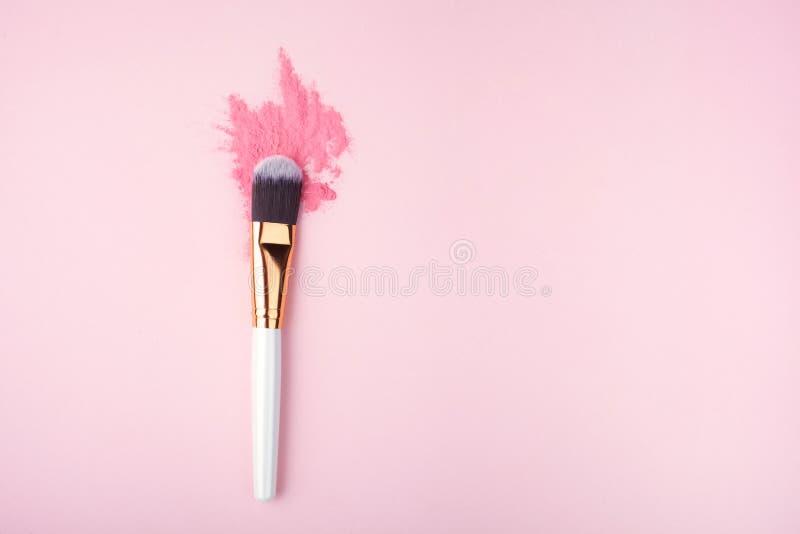 Spazzola di trucco su fondo rosa con la polvere variopinta del pigmento Vista superiore fotografia stock libera da diritti
