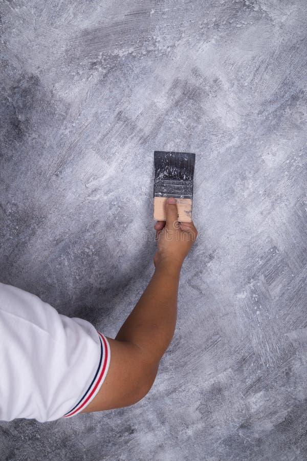 Spazzola di uso della mano per stile concreto del sottotetto della pittura di colore sulla parete immagini stock libere da diritti