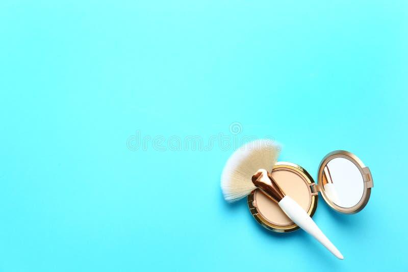 Spazzola e cipria professionali di trucco su fondo blu-chiaro, vista superiore fotografia stock libera da diritti