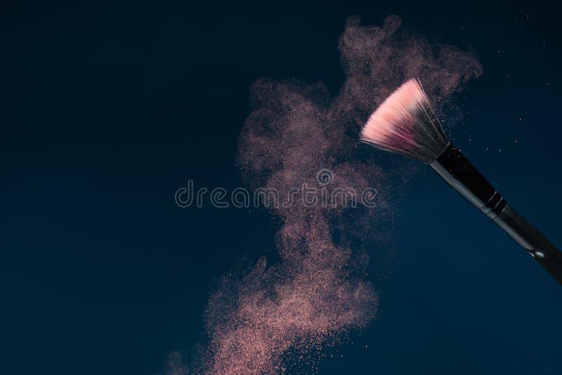 Spazzola nera professionale di trucco con polvere rosa immagine stock
