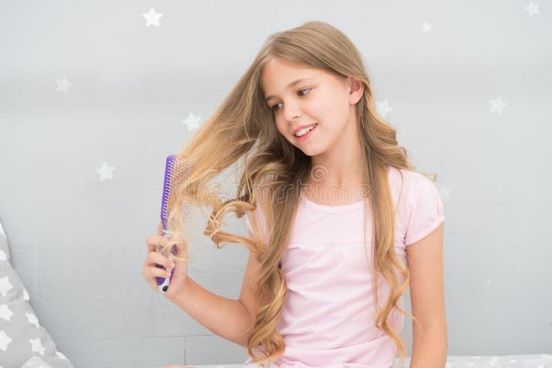 Spazzola per i capelli o pettine riccia della tenuta dell'acconciatura del bambino Applichi l'olio prima della pettinatura dei ca fotografia stock libera da diritti