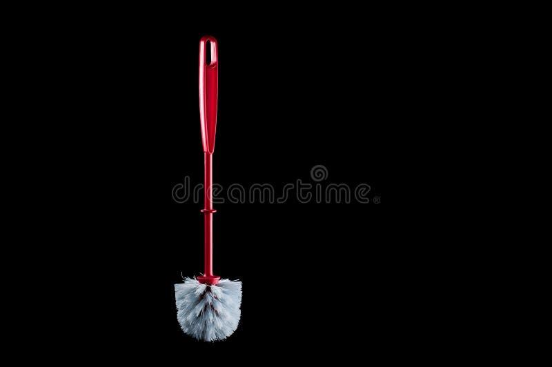 Spazzola separata per pulire la toilette con una maniglia rossa su un fondo nero, isolato immagini stock libere da diritti