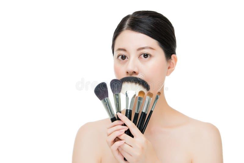 Spazzole castane della tenuta della donna asiatica del ritratto di bellezza per trucco immagine stock libera da diritti