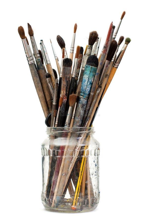 Spazzole di pittura sporche Assorted in boccetta di vetro immagine stock