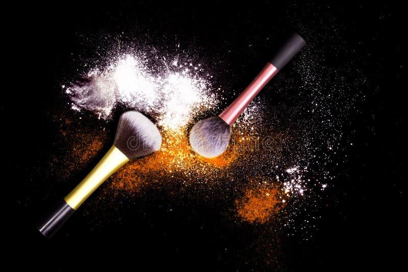 Spazzole di trucco con polvere variopinta su fondo nero Polvere di stelle di esplosione con i colori luminosi Polvere bianca ed a fotografia stock