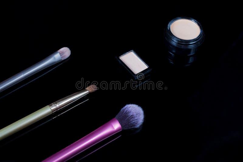 Spazzole di trucco su fondo nero Cosmetici, modo, bellezza, fascino Accessori per l'ombra di Eye del truccatore, correttore, immagini stock libere da diritti