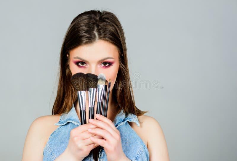 Spazzole differenti Cura di pelle Concetto dei cosmetici di trucco Correttore di incarnato Negozio delle estetiche La ragazza app fotografie stock libere da diritti