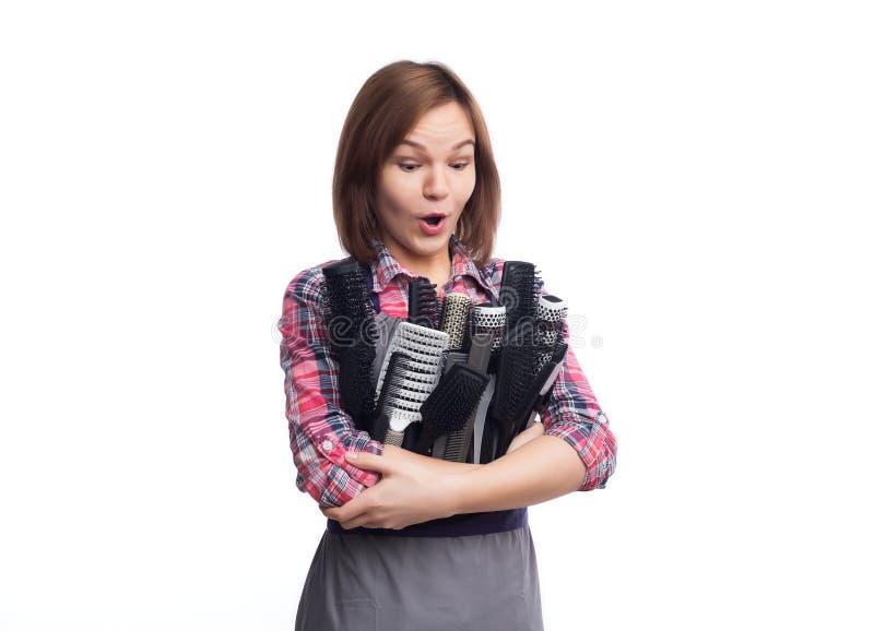 Spazzole e pettine femminili della tenuta del parrucchiere a fondo grigio immagine stock libera da diritti