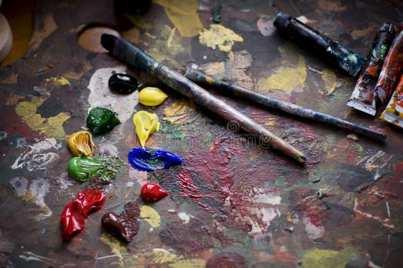Spazzole e vecchio pallet del pittore fotografia stock