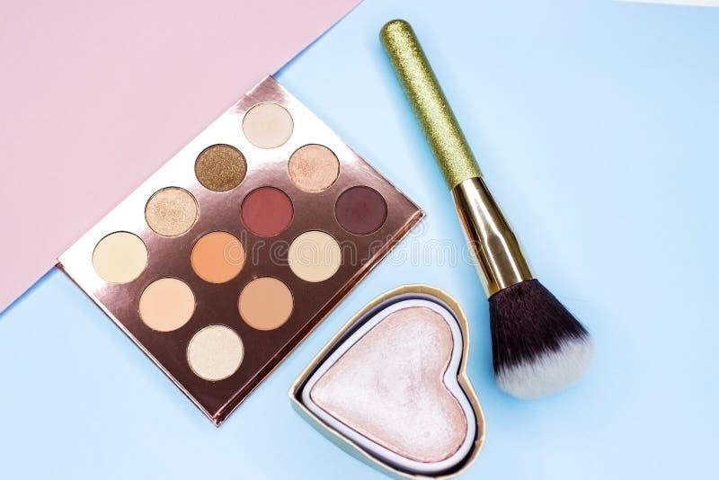 Spazzole per trucco, struttura con i cosmetici su fondo rosa e blu fotografia stock
