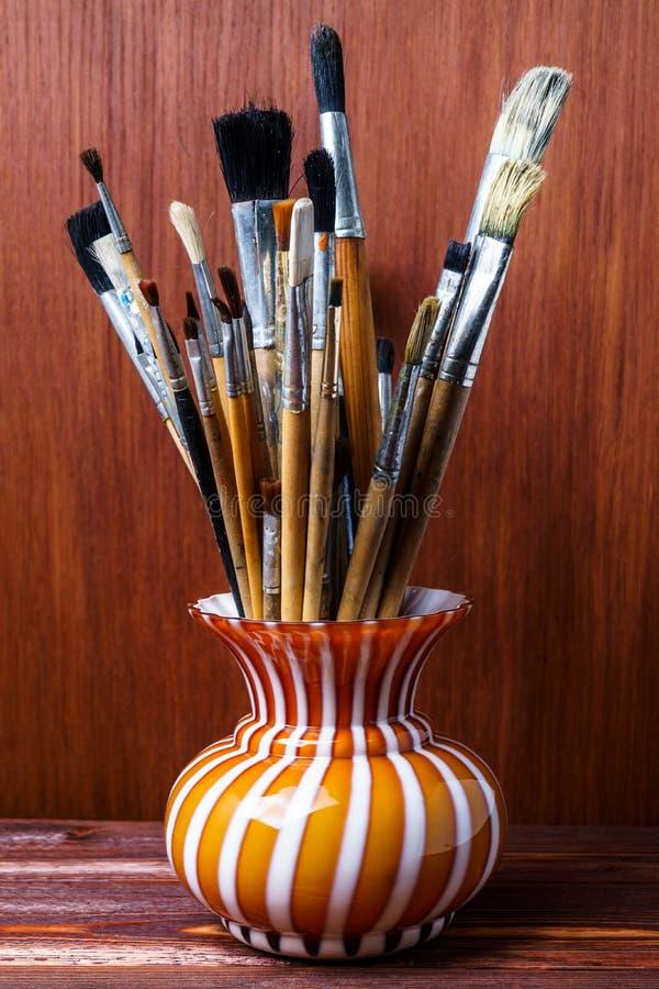 Spazzole sporche assortite in un vaso su un fondo di legno Pennelli utilizzati dell'artista in un vaso fotografia stock