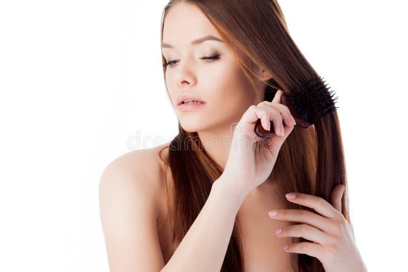 Spazzoli i suoi capelli Ragazza attraente con capelli lunghi Ritratto di bella giovane donna che per mezzo di un pettine immagini stock