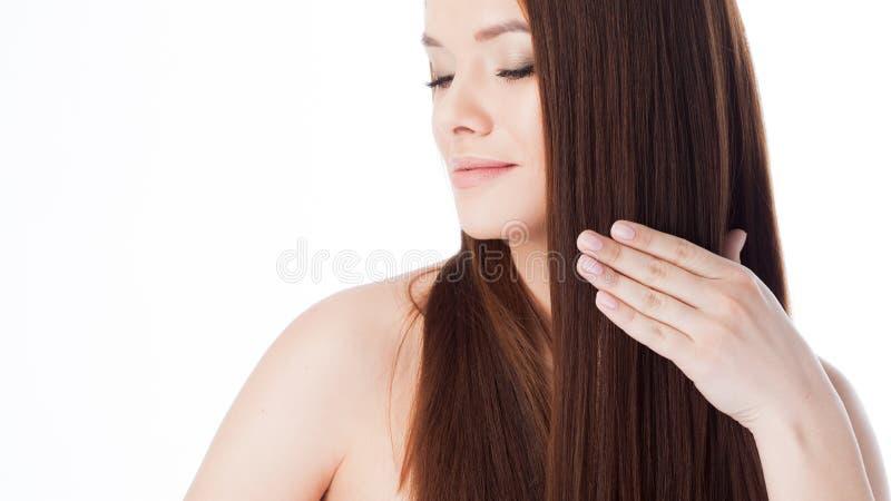 Spazzoli i suoi capelli Ragazza attraente con capelli lunghi Ritratto di bella giovane donna che per mezzo di un pettine immagini stock libere da diritti