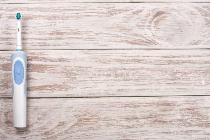 Spazzolini da denti elettrici sui precedenti di legno con lo spazio della copia per il vostro testo Vista superiore immagine stock