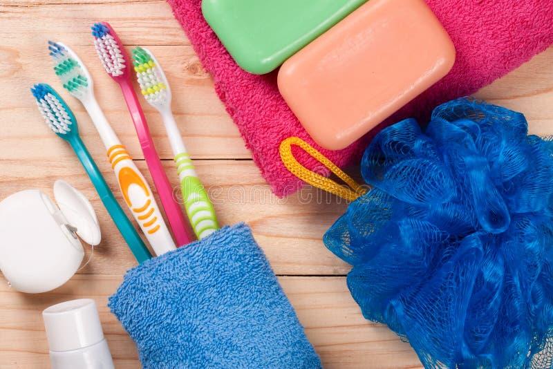 Spazzolini da denti, sapone, spugna, asciugamano su una tavola di legno Prodotti di igiene Vista superiore immagini stock libere da diritti