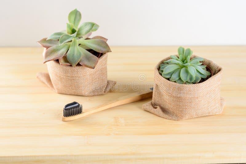 Spazzolino da denti di bambù con il dentifricio in pasta del carbone immagine stock
