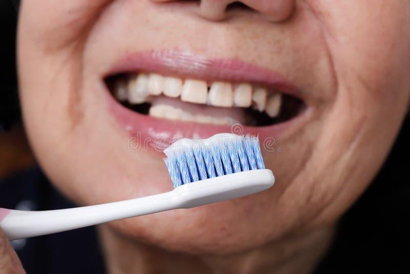 Spazzolino da denti di prova di uso della donna anziana asiatica, tremore della mano fotografia stock