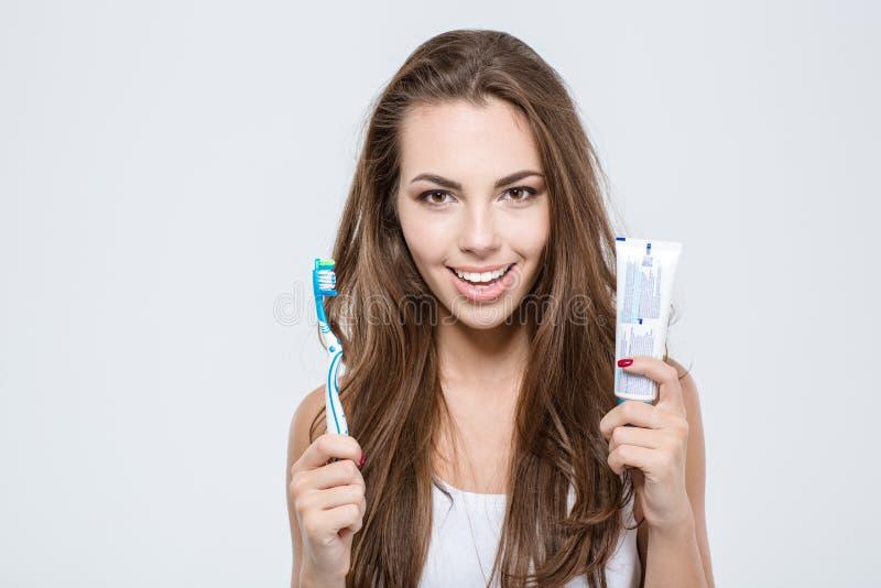 Spazzolino da denti e dentifricio in pasta felici della tenuta della donna fotografie stock libere da diritti